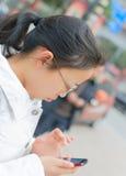 女孩使用电话 免版税库存图片