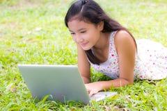 女孩使用膝上型计算机 库存照片