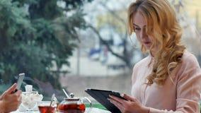 女孩使用他们的从工作的断裂喝咖啡,闲谈和使用数字式片剂 免版税图库摄影
