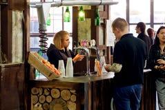 女孩侍酒者倒苹果汁在酒吧 免版税库存照片
