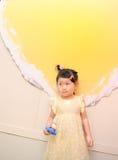 女孩依靠黄色墙壁 免版税图库摄影