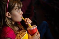 女孩侧视图饮用饮料和玉米花在电影期间 免版税库存图片