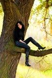 女孩俏丽的坐的结构树 免版税图库摄影