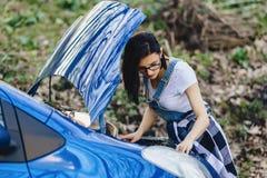 女孩修理有一个开放敞篷的汽车在路 免版税库存照片