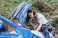 女孩修理有一个开放敞篷的汽车在路 库存照片