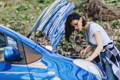 女孩修理有一个开放敞篷的汽车在路 免版税图库摄影