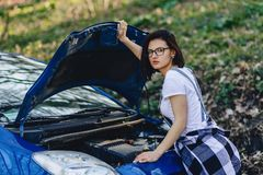 女孩修理有一个开放敞篷的汽车在路 免版税库存图片