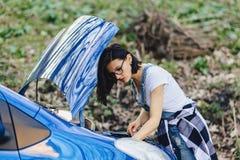 女孩修理有一个开放敞篷的汽车在路 库存图片
