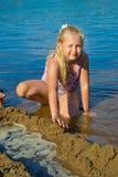 女孩修造沙子城堡 库存照片