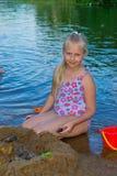 女孩修造沙子城堡 库存图片