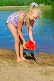 女孩修造沙子城堡 图库摄影