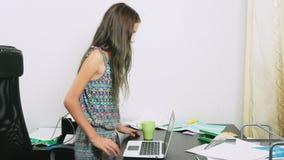 女孩倾倒了在膝上型计算机之上的茶 做家庭作业,在网上学会,4k特写镜头, 股票录像