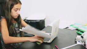 女孩倾倒了在膝上型计算机之上的茶 做家庭作业,在网上学会,4k特写镜头, 影视素材