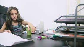 女孩倾倒了在膝上型计算机之上的茶 做家庭作业,在网上学会,4k特写镜头, 股票视频