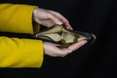 女孩倾吐从钱包,黑背景,特写镜头女性的硬币 免版税库存照片