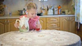 女孩倾吐的汁液到玻璃和饮料里 股票录像