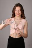 女孩倾吐的水到葡萄酒杯里 关闭 灰色背景 免版税图库摄影