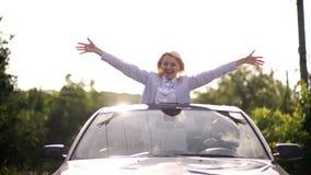 女孩倾斜了入舱口盖和乘驾沿路在一辆蓝色汽车有有胡子的人的 r ?? 影视素材