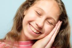 女孩假装睡眠手微笑的表情 图库摄影