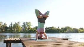 女孩做与她的盘的腿的一headstand 瑜伽 股票录像