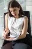 女孩做在一本光滑的杂志的笔记 库存图片