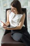 女孩做在一本光滑的杂志的笔记 图库摄影