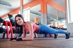 女孩做在健身房的板条 免版税库存图片