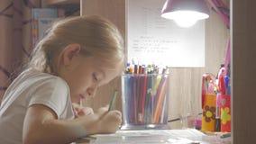 女孩做它的家庭作业在桌上在灯的光下 小公主创造性的爱好  生活方式  股票视频