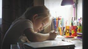 女孩做它的家庭作业在桌上在灯的光下 小公主创造性的爱好  生活方式  影视素材