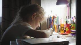 女孩做它的家庭作业在桌上在灯的光下 小公主创造性的爱好  生活方式  股票录像