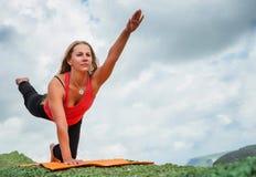 女孩做平衡的瑜伽锻炼 免版税库存图片