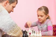 女孩做接下来的步骤,当下与教练时的棋 免版税图库摄影