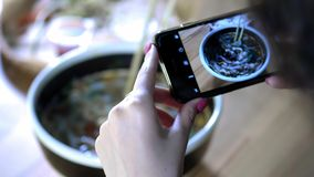 女孩做照片食物在智能手机 与朋友的份额食物照片在人脉的 与亚洲咖啡馆 股票视频