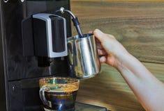 女孩做煮沸的牛奶 对此,她使用一特别咖啡机 免版税库存照片