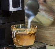 女孩做煮沸的牛奶 对此,她使用一特别咖啡机 库存照片