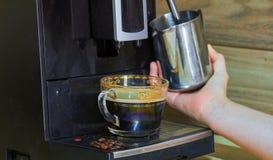 女孩做煮沸的牛奶 对此,她使用一特别咖啡机 库存图片