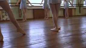 女孩做芭蕾锻炼在芭蕾教训期间在有磨损的地板的教室 影视素材