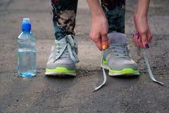 女孩停止跑栓在鞋子的鞋带 免版税库存图片