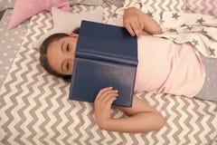 女孩儿童位置床读了书顶视图 孩子准备上床   女孩孩子放松和读 图库摄影