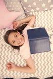 女孩儿童位置床读了书顶视图 孩子准备上床 宜人的时间在舒适卧室 女孩逗人喜爱孩子的长发 图库摄影