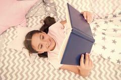 女孩儿童位置床读了书顶视图 鼓励有用的习性 孩子准备上床 宜人的时间在舒适卧室 免版税图库摄影
