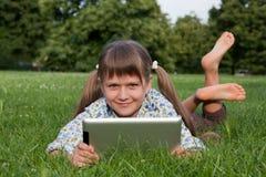 女孩儿童藏品片剂无线计算机rel 免版税库存照片