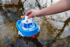 女孩充当有一艘小玩具船的一条河 库存图片