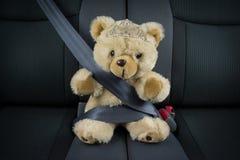 女孩公主玩具熊在有冠状头饰的一辆汽车坐 免版税库存照片