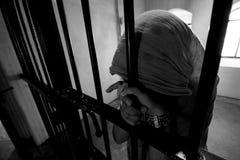 女孩关在监牢里 免版税库存照片