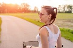 女孩关闭与在夏天日落的自行车在路在城市公园 在街道下工作的循环在夏天日落 库存照片