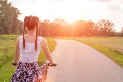 女孩关闭与在夏天日落的自行车在路在城市公园 在街道下工作的循环在夏天日落 免版税库存图片