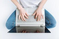 女孩关闭的拇指,您在演播室按膝上型计算机的键,背景 库存照片