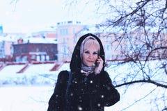 女孩冬天街道谈话电话 库存照片
