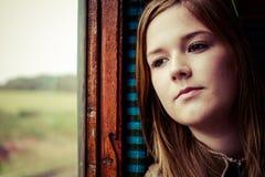 女孩凝视低谷窗口,当旅行乘火车时 库存图片